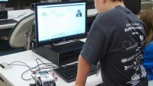 A past participant from College for Kids and Middle School University works on a computer robotics project.