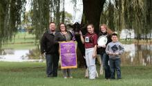 Ryan Weigel and his family with their prize winning cow, Altitude, which Weigel and partners purchased at the Pioneer Dairy Club Classic in 2000.